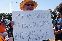 "Stan holds a sign saying ""My retirement is on Wall Street, but What the F***?"" at the Occupy Orange County, Irvine camp on November 5."