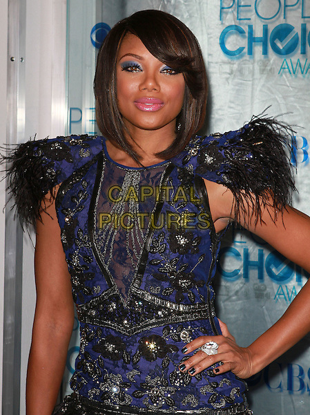 TIFFANY HINES .2011 People's Choice Awards held at Nokia Theatre L.A. Live, Los Angeles, California, USA, 5th January 2011..half length blue black dress shoulder pads feathers hand on hip lace beaded ring .CAP/ADM/KB.©Kevan Brooks/AdMedia/Capital Pictures.