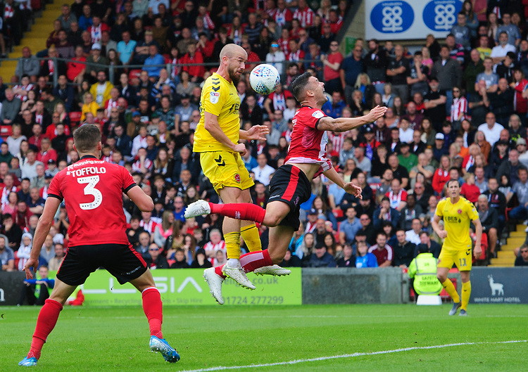 Fleetwood Town's Paddy Madden vies for possession with Lincoln City's Jason Shackell<br /> <br /> Photographer Chris Vaughan/CameraSport<br /> <br /> The EFL Sky Bet League One - Lincoln City v Fleetwood Town - Saturday 31st August 2019 - Sincil Bank - Lincoln<br /> <br /> World Copyright © 2019 CameraSport. All rights reserved. 43 Linden Ave. Countesthorpe. Leicester. England. LE8 5PG - Tel: +44 (0) 116 277 4147 - admin@camerasport.com - www.camerasport.com