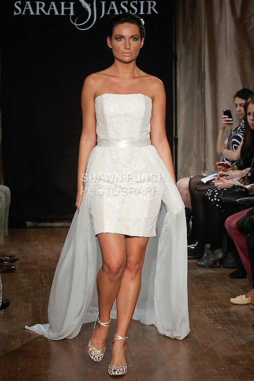 """Model walks runway in a Talia Bridal dress -  blush taffeta lace/sequin strapless dress with chiffon over skirt, by Sarah Jassir, for the Sarah Jassir Spring 2013 """"La Reve: The Dream"""" collection, during Bridal Fashion Week New York."""
