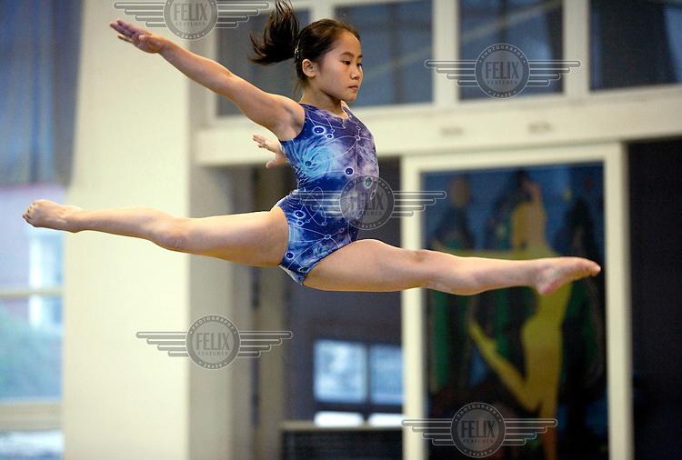 A young gymnast works on her balance beam gymnastics skills.