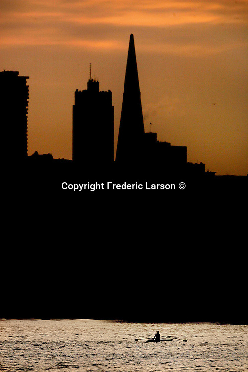 An rowboat sailed past the San Francisco skyline the sunrise silhouetted the cities skyline...
