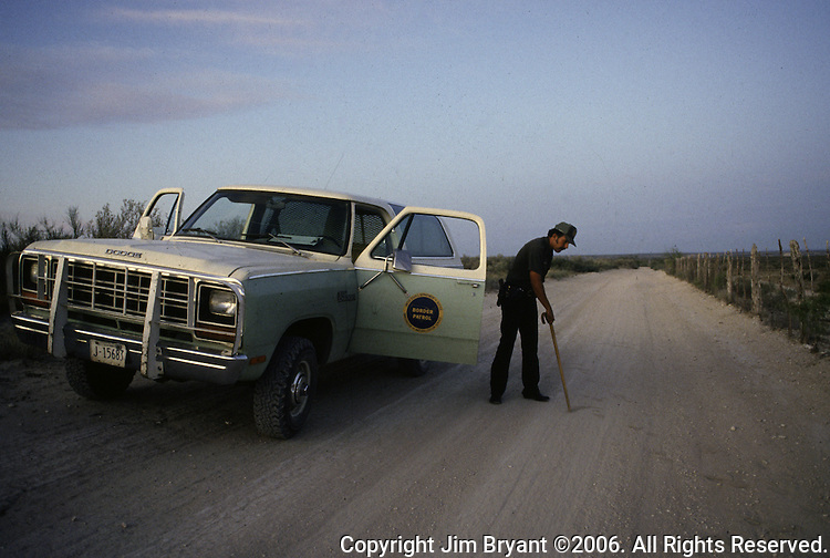 A U.S. Border Patrol agent in Del Rio, Texas searches for shoeprints on a grated roadway. While the traditional mission of the United States Border Patrol has always been the detection and prevention of the illegal entry of aliens and smuggling of illegal contraband into the United States anywhere other than a designated port-of-entry, the dawn of the age of terrorism within our nation has added a new and high priority mission: to detect and prevent the entry of terrorists and their weapons into the United States. Jim Bryant Photo..©2006. All Rights Reserved.
