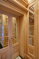 A pair of mirrored doors with wood panelling and gold handles.