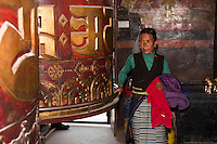 Bodhnath, Nepal.  Buddhist Worshiper Turning Prayer Wheel, Tsamchen Gompa.