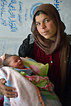 Raghad Al-Hussein, a 30-year old refugee from Syria, holds her newborn child inside their makeshift shelter in the village of Jeb Jennine, in Lebanon's Bekaa Valley. The wall behind her is made from potato sacks. She and other refugees in the area are being assisted by International Orthodox Christian Charities and other members of the ACT Alliance..