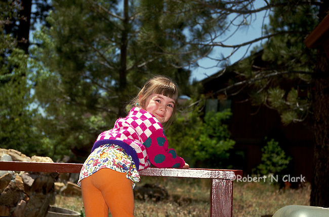 Girl in mountain setting standing on fence rail and smiling at the camera