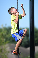 NWA Democrat-Gazette/DAVID GOTTSCHALK Peyton Boliver, 9, climbs Monday, August 12, 2019, the rope on his way to ring the bell at the Fitcore Extreme Obstacle Course in Farmington. The new course features many obstacles to challenge and increase stability, balance and upper and lower body strength.