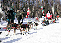 Spectators watch Italian musher Fabrizio Lovati along the trail in Anchorage on Saturday March 1st during the ceremonial start day of the 2008 Iidtarod Sled Dog Race.