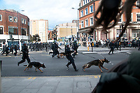 Riot police run with dogs run down Mare Street in the London borough of Hackney chasing rioters. London saw the beginnings of riots on Saturday evening, after a peaceful protest in response to the shooting by police of Mark Duggan during an attempted arrest, escalated into violence. By the third night of violence, rioting had spread to many areas of the capital and to other cities around the country.