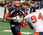 SIOUX FALLS, SD - MAY 16:  Chris Dixon #2 from the Sioux Falls Storm eyes yardage past Jordan Morgan #94 form the Bemidji Axemen in the first half of their game Saturday night at the Sioux Falls Arena. (Photo by Dave Eggen/Inertia)