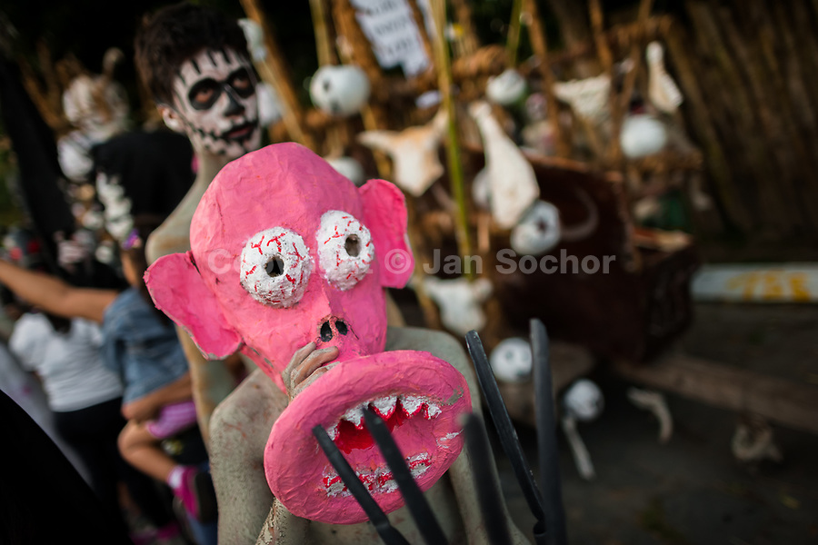 A Salvadoran boy, wearing a pink mask, performs an indigenous mythology character in the La Calabiuza parade at the Day of the Dead festivity in Tonacatepeque, El Salvador, 1 November 2016. The festival, known as La Calabiuza since the 90s of the last century, joins Salvador's pre-Hispanic heritage and the mythological figures (La Sihuanaba, El Cipitío, La Llorona etc.) collected from the whole Central American region, together with the catholic All Saints Day holiday and its tradition of honoring the dead relatives. Children and youths only, dressed up in scary costumes and carrying painted carts, march from the local cemetery to the downtown plaza where the party culminates with music, dance, drinking and eating pumpkin (Ayote) with honey.