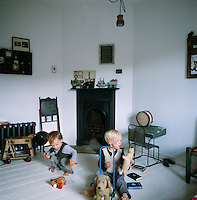 Two boys playing with traditional toys in a retro styled room,