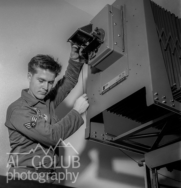 A/2C Ricky Lapado in the base photo Lab.<br /> <br /> March 1964: CAFB, California<br /> Staff of the Valley Bomber, 93rd Bomb Wing, Directory of Information, SAC<br /> Photo by Al Golub/Golub Photography <br /> <br /> Castle is named for Brigadier General Frederick W. Castle, who died on Dec. 24, 1944 flying his 30th bombing mission. He died leading an armada of 2000 B-17s on a strike against German airfields. On the way to the target, an engine failure over Liege, Belgium caused his bomber to fall behind, where it was attacked by Germans and caught fire. He ordered his men to bail out but stayed alone at the controls of the flaming Flying Fortress until it crashed. The entire crew, except Gen. Castle and one airman killed before the bailout order, survived. Gen. Castle received a Medal of Honor posthumously for his bravery.<br /> <br /> Castle became home to the 93rd Bombardment Wing in 1947. Aircraft stationed at Castle included B-29, B-17 and C-54 aircraft, with B-50 bombers arriving in 1949. In 1954, B-47 bombers arrived.  On June 29, 1955, Castle received the Air Force's first B-52. These heavy bombers can hold the equivalent of three railroad cars' worth of fuel. The first Air Force KC-135 jet tanker arrived May 18, 1957<br /> <br /> Castle was selected for closure under the Defense Base Closure and Realignment Act of 1990 during Round II Base Closure Commission deliberations (BRAC 91). The last of the B-52s left the base in 1994, followed by the departure of the last of the KC-135s in early 1995. The base closed September 30, 1995.