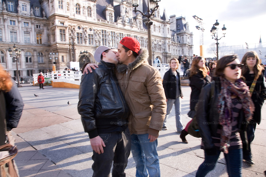 """Valentine's day, kissing at the Paris Townhall, inspired by and in hommage to Robert Doisneau's famous picture, Give a """"Baiser de l'Hotel de Ville"""" was called for by 'Vive Paris Capitale' and 'merciparis.fr', to Parisiens and people who hold Paris close to their hearts. This celebration of the most beautiful day of the year for lovers, a Valentine's Day in romantic Paris, brought together a mixture of couples, amateur photographers, journalists and television, to witness lovers kissing and just celebrate love.///Lascars Gays Steeve and Ryan kissing in front of the Hotel de Ville (model released)"""