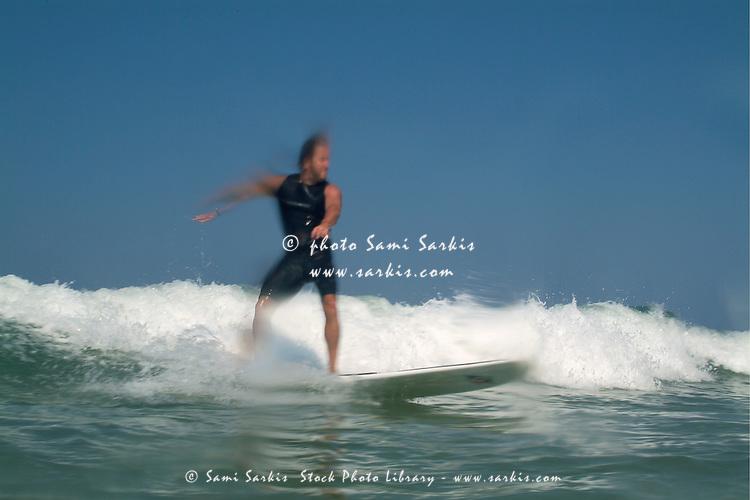 Man surfing waves at Le Porge beach, Bordeaux, France.