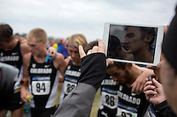 A photographer uses an iPad to capture Colorado's Blake Theroux as the team speaks to media following their title during the NCAA Cross Country Championships in Terre Haute, Ind. on Saturday, Nov. 22, 2014. (James Brosher, Special to the Denver Post)