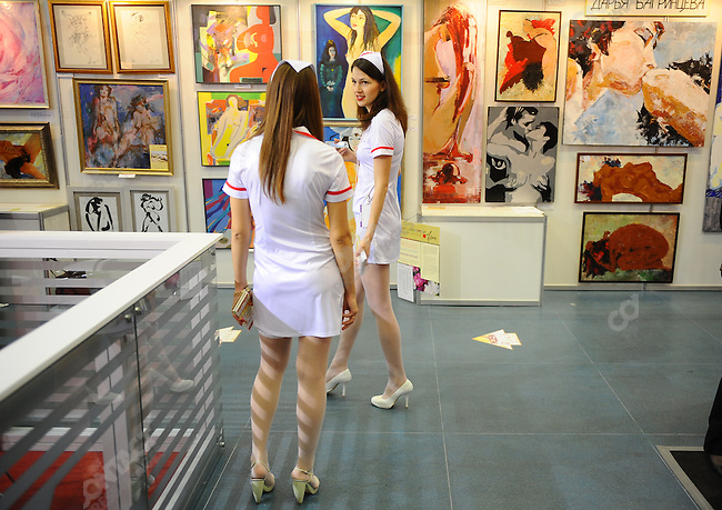 At the X-Show in Moscow, a show with stands selling and promoting businesses involved in the erotic industry, girls dressed as nurses handed out flyers stopped for a photo. Moscow, Russia, May 28, 2010