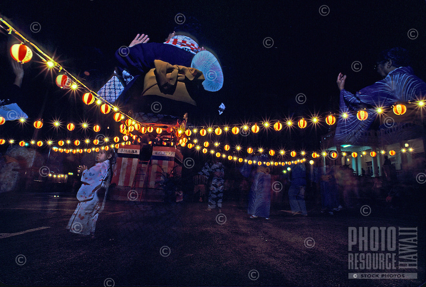 Nighttime shot of the Asian Obon festival at Hon Wanji Mission, featuring women dressed in traditional kimono costume dancing under multi strings of lanterns