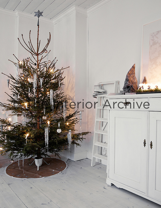 Simple strands of silver lamenta and fairy lights adorn the Christmas tree in the living room