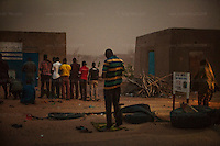 AGADEZ, NIGER &mdash; <br /> Passengers pray during a sand storm at the side of the road on their journey to the city of Agadez, Niger. During the many police check-points, migrants were routinely extorted for money by the police, who held their travel documents until the money was paid. Migrants are routinely harassed by both police and military personnel along the various countries they travel through before reaching their final destination.