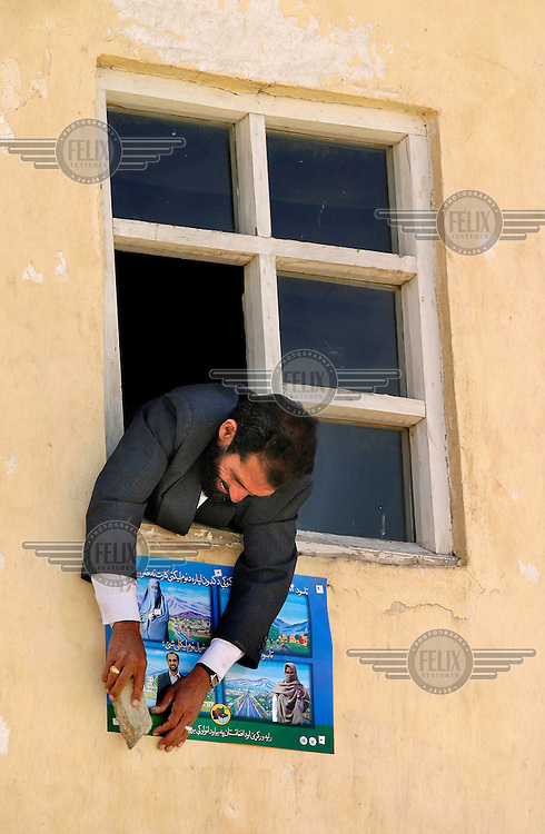 A man fastens a poster about the upcoming local elections on a school wall. The introduction of democracy has prompted a need for information on politics and democratic procedures.