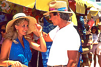 Colorful tourist couple shopping at island straw market