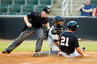 Mark Haddow (21) of the Kannapolis Intimidators is tagged out at home plate by West Virginia Power catcher Elias Diaz as home plate umpire Junior Valentine looks on at CMC-Northeast Stadium on August 17, 2012 in Kannapolis, North Carolina.  (Brian Westerholt/Four Seam Images)