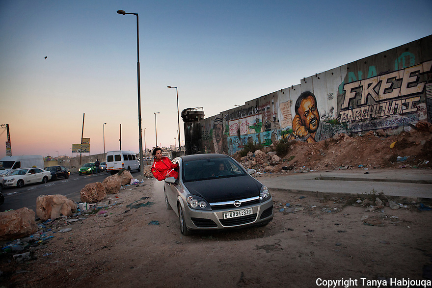 "Mona Ennab, a ""Speed Sister"" from Ramallah, trains with colleague Noor Daoud at the Qalandia check point during a quiet lull during iftar in Ramadan. Open spaces for practicing racing and drifting are limited in the West Bank."