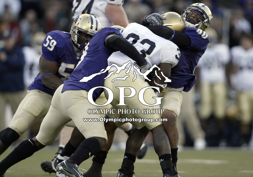 October 25, 2008:   Washington defensive players #40 Mason Foster(right), #8 Nate Williams (center) and #59 Darrion Jones (right) drag down Notre Dame running back #33 Robert Hughes.  Notre Dame defeated Washington 33-7 at Husky Stadium in Seattle, Washington.  .