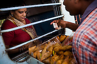 Food vendors sell samosa through the grilled windows of the sleeper class coach to train passengers of the Himsagar Express 6318 as it stops for 20 minutes at Erode Junction stn., Tamil Nadu on 9th July 2009.. .6318 / Himsagar Express, India's longest single train journey, spanning 3720 kms, going from the mountains (Hima) to the seas (Sagar), from Jammu and Kashmir state of the Indian Himalayas to Kanyakumari, which is the southern most tip of India...Photo by Suzanne Lee / for The National