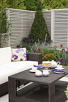 Modern sophisticated upscale patio with black and white color theme, fence, evergreens, black leaved plants, tea service on table, sofa couch lounge for a beautiful room outdoors in home landscaping living