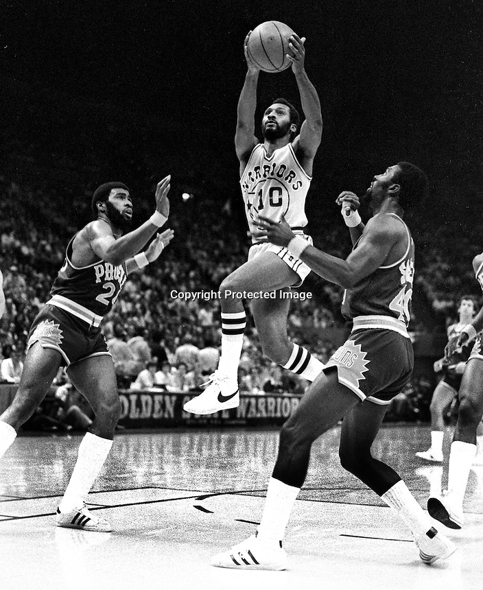 Golden State Warrior Charles Johnson drives on Gar Heard and Ricky Sobers of the Phoenix Suns playoff game 1976, (photo by Ron Riesterer)