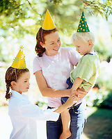 A teenage girl holding a shy boy and a young girl all wearing party hats at a birthday party