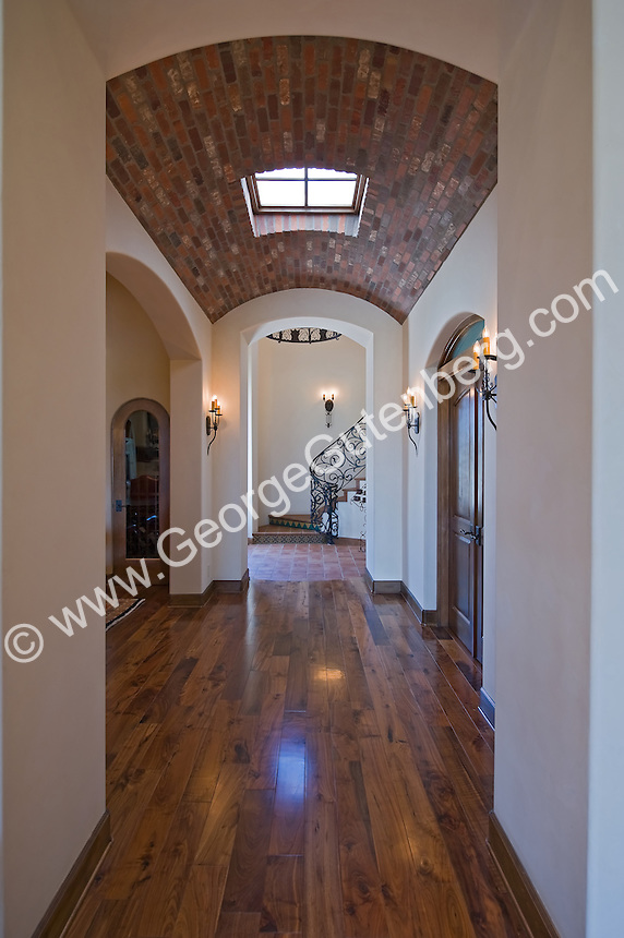 Beautiful hallway with coved brick ceiling leads to wrought iron spiral staircase