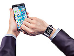 Hands of a person wearing Samsung Galaxy Gear watch and holding Galaxy Note 3 smartphone isolated on white background
