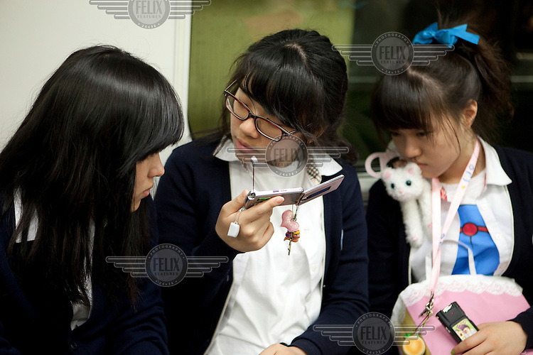 Schoolgirls listen to a broadcast on a mobile phone whilst travelling on the Seoul Metropolitan Subway.