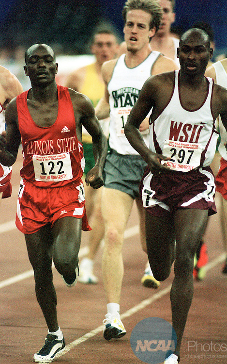 "MAR 6, 1999: Bernard Lagat (right) of Washington State runs races toward the finish line of the men's mile in the Men's and Women's Division I Indoor Track Championship held at the RCA Dome in Indianapolis, IN. Lagat took first place in the event with a time of 3:55.65"""". Eric Kane/NCAA Photos."