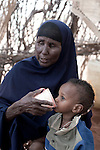 MATHAHALIBAH, KENYA - JULY 4: Mohammedek Siyad, 21 months old, is given water by his grandmother while visiting a Save the Children outreach site in the location. The team examined about thirty children, among them several severely malnourished. Mohammedek's grandmother Habiba Sahal came with him to the outreach site to receive some food and medicine. His mother left three months ago with their remaining livestock. Forced away due to the sever drought in the area. She is expected back when rain falls again. Mohammedek is now being cared by his grandmother. Two successive poor rains, entrenched poverty and lack of investment in affected areas have pushed millions of people into a fight for survival in the Horn of Africa. This is the driest this area have been since sixty years. (Photo by Per-Anders Pettersson)