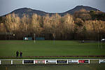 Two spectators are framed by the Eildon hills in the background as they await kick-off before Gala Fairydean Rovers host Gretna 2008 in a Scottish Lowland League match at Netherdale, Galashiels. The home club were established in 2013 through a merger of Gala Fairydean, one of Scotland's most successful non-League clubs, and local amateur club Gala Rovers. The visitors were a 'phoenix' club set up in the wake of the collapse of the original club, which had competed for a short time in the 2000s before going bankrupt. The home aside won this encounter 4-1 watched by a crowd of 120 at a stadium which features one of the country's most notable stands, a listed building constructed in 1964 but at the time of this fixture closed to spectators on safety grounds.