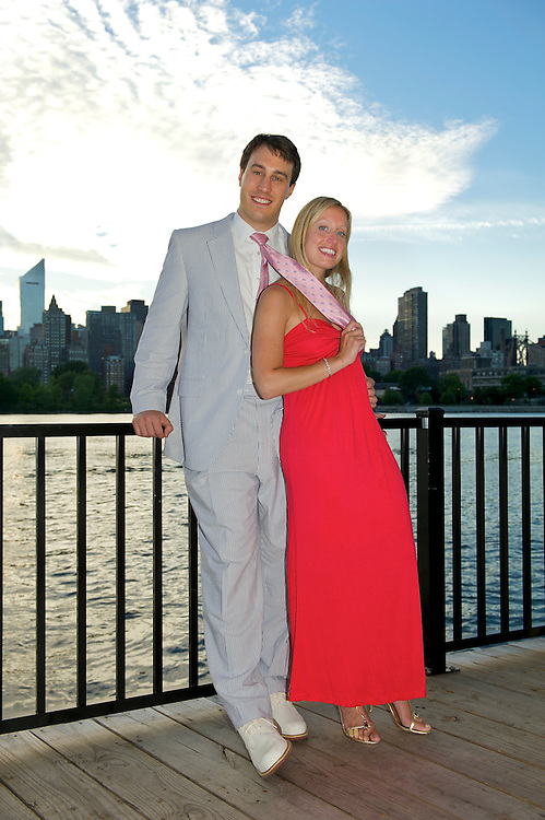 Engaged couple at The Water's Edge, Long Island City with The East River and Manhattan skyline in the background.