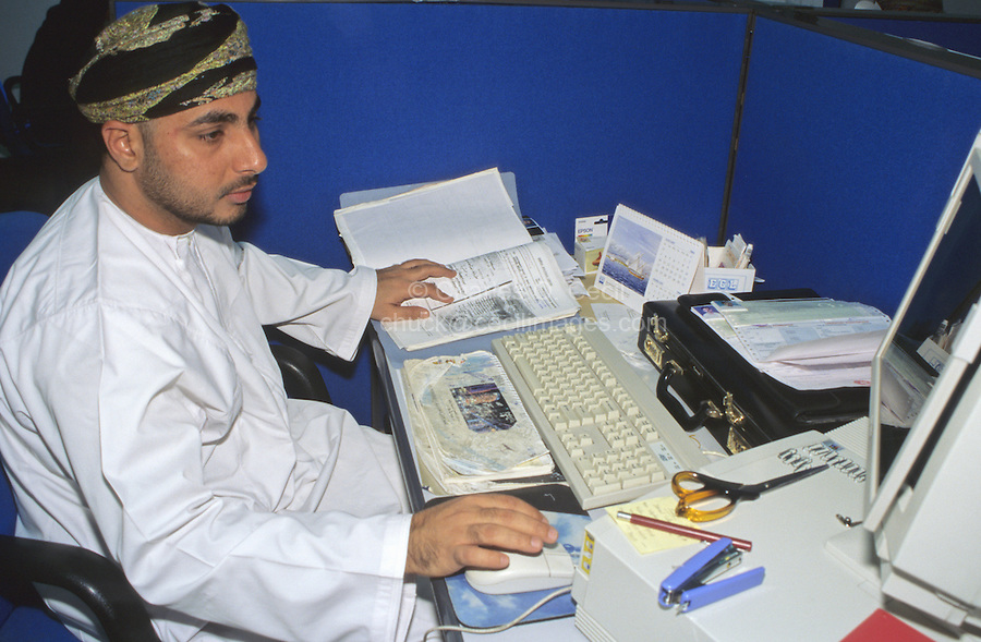 Muscat, Oman, Arabian Peninsula, Middle East - Omani Computer Worker, Bahwan Cybertek.  He wears the traditional Omani robe, a dishdasha, and headdress, the msarr or massar.