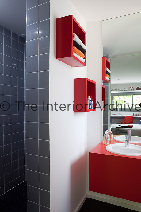 Red wall-mounted boxes are designed to match the washstand in striking contrast to the dark grey tiled walk-in shower in this bathroom