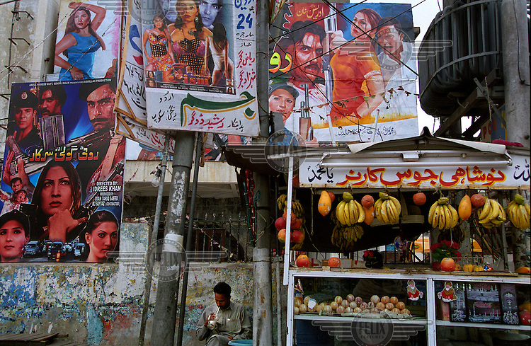 A man enjoys a fruit drink at a roadside stall in the cinema district of Lahore under posters advertising the Lollywood films which are made locally.