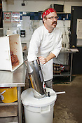 Chef James Naquin loads ground beef and pork into a sausage maker to produce bratwurst Durham, N.C., July 7, 2012.