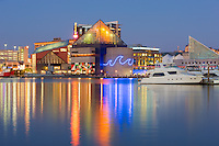 Lights from the National Aquarium reflect off the waters of the Inner Harbor during evening twilight in Baltimore, Maryland.
