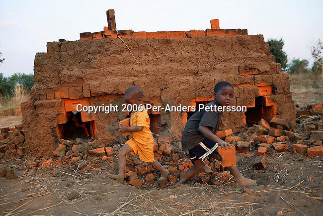MPHANDULA, MALAWI - AUGUST 17: Unidentified children carry bricks from an oven on August 17, 2006 in Mphandula village, about 30 miles outside Lilongwe, Malawi. Mphandula is a poor village in Malawi, without electricity or clean water. Nobody owns a car or a mobile phone. Most people live on farming. About 7000 people reside in the village and the chief estimates that there are about five-hundred orphans. Many have been affected by HIV/Aids and many of the children are orphaned. A foundation started by Madonna has decided to build an orphan center in the village through Consol Homes, a Malawi based organization. Raising Malawi is investing about 3 million dollars in the project and Madonna is scheduled to visit the village in October 2006. Malawi is a small landlocked country in Southern Africa without any natural resources. Many people are affected by the Aids epidemic. Malawi is one of the poorest countries in the world and has about 1 million orphaned children. (Photo by Per-Anders Pettersson/Exclusive by Getty Images)