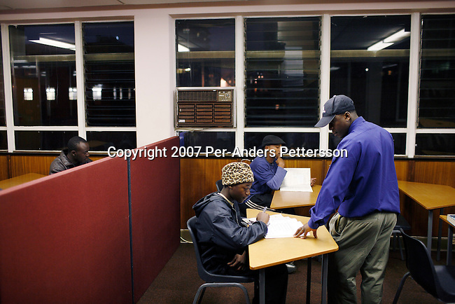 JOHANNESBURG, SOUTH AFRICA JULY 24: A teacher holds a night class for refugees from Zimbabwe in the Central Methodist Church on July 24, 2007 in central Johannesburg, South Africa. Thousands of refugees sleep here in a four-story building with in bad conditions. Millions of Zimbabweans has fled the country since 2000, to look for a better life in South Africa. .(Photo by Per-Anders Pettersson/Getty Images).