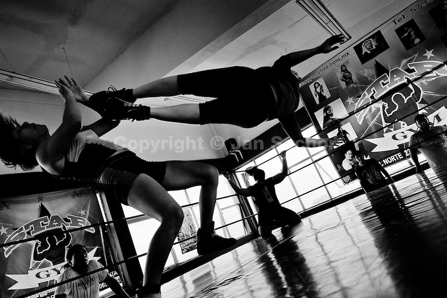 "A female Lucha libre wrestler Sexy Star kicks her sparring partner during the training at a combat sports gym in Mexico City, Mexico, 3 May 2011. Lucha libre, literally ""free fight"" in Spanish, is a unique Mexican sporting event and cultural phenomenon. Based on aerial acrobatics, rapid holds and the use of mysterious masks, Lucha libre features the wrestlers as fictional characters (Good vs. Evil). Women wrestlers, known as luchadoras, often wear bright shiny leotards, black pantyhose or other provocative costumes. Given the popularity of Lucha libre in Mexico, many wrestlers have reached the cult status, showing up in movies or TV shows. However, almost all female fighters are amateur part-time wrestlers or housewives. Passing through the dirty remote areas in the peripheries, listening to the obscene screams from the mainly male audience, these no-name luchadoras fight straight on the street and charge about 10 US dollars for a show. Still, most of the young luchadoras train hard and wrestle virtually anywhere dreaming to escape from the poverty and to become a star worshipped by the modern Mexican society."