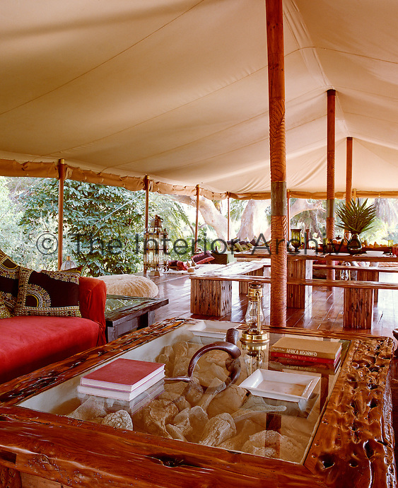 The canvas roof of the 'living' tent is supported by a series of central wooden pillars that run the length of the tent